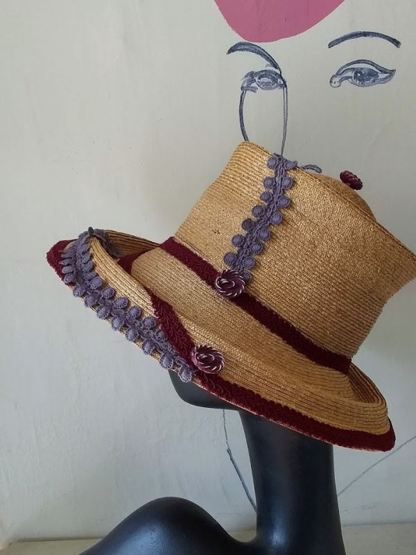 Straw hat with violet and wine colored trim.
