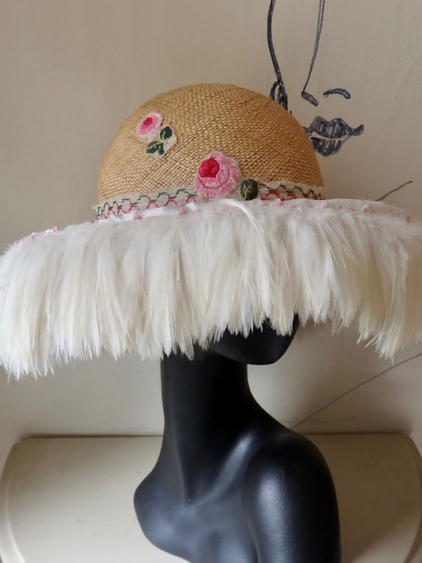 Straw hat with pink flowers and white feathers flowing from the brim.
