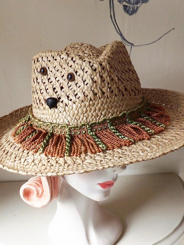 Straw hat with brown and green tassels and a face made from buttons.