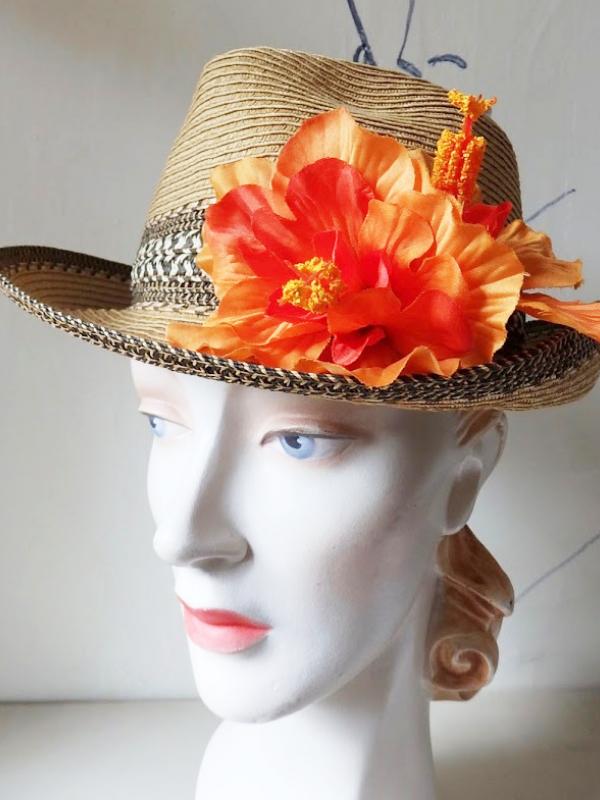 A straw hat with an orange flower.