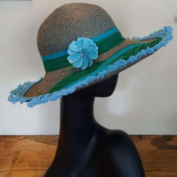 Straw hat with a blue flower and green and blue trim.