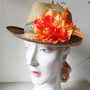 A straw hat with an orange flower.